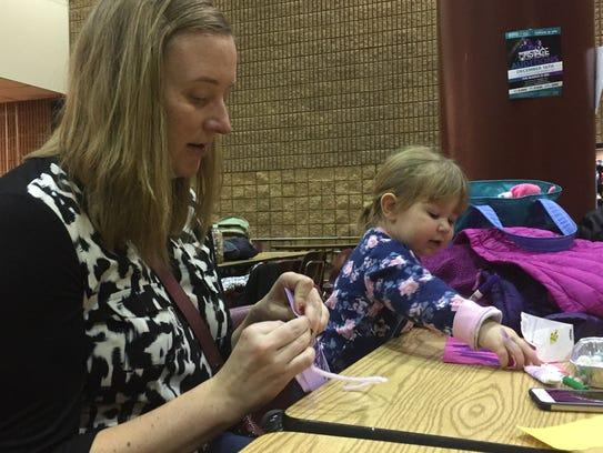 Eileen Lih and her daughter, Emilia, 2, make tiaras