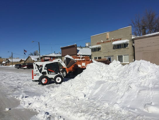 Tim LaBuea uses a Bobcat to load snow onto a truck driven by Larry Geyer in Big Sandy.