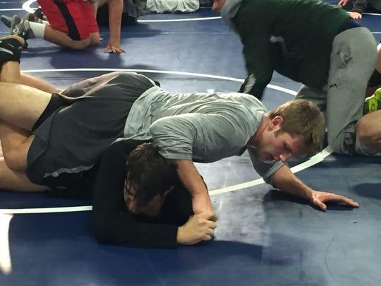 Thousand Oaks High senior Carl McQuillan, top, is wrestling