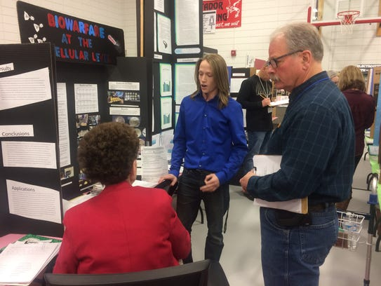 A student presents his science project to judges during the Farmington Municipal School District Science Fair at Hermosa Middle School on Saturday.