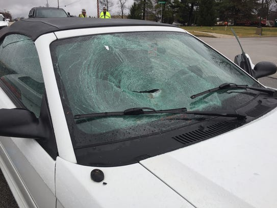 The busted windshield of a Ford Mustang that struck