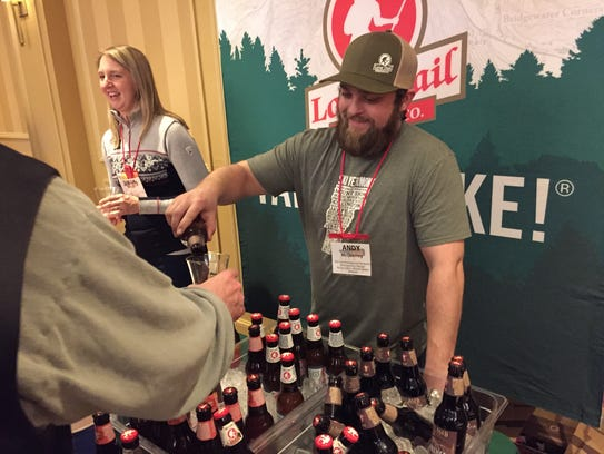 Andy McQuerrey, marketing events manager for Vermont-based Long Trail Brewing, pours a beer in March for an attendee of the Beer Marketing & Tourism Conference in South Burlington.
