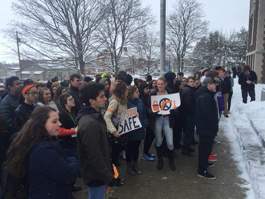 Students hold gun safety signs at a walkout that was