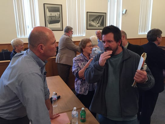 Court-appointed receiver Geoffrey Treece (left) talks with an area resident following the conclusion of a town hall-style meeting in March at the Baxter County Courthouse to discuss a yearly $18 solid waste fee. A Berryville resident has sued the Ozark Mountain Solid Waste District over the service fee's collection.