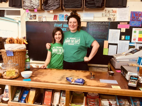 """Georgia Chojnicki, left, and Mary Alberti pose in March 2018 at the East Warren Market while wearing """"Mind the Gap"""" T-shirts in honor of mud season and the conditions along the """"Roxbury Gap,"""" a road that connects Roxbury and Warren.The T-shirts are for sale at the market."""