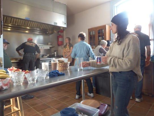 Arlinda, Fasliu, a server at Agape Cafe, looks on a