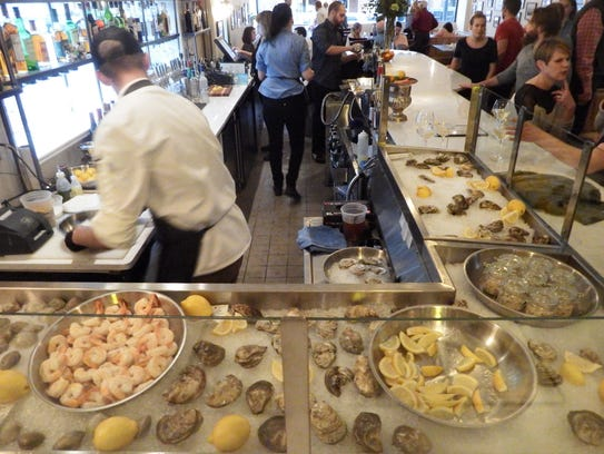 The main dining room and raw bar are shown at St. Burch