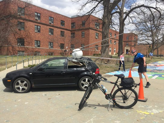 A Drake University police officer places cones around