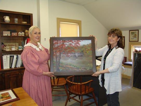Stacie Stein and Lynda Daniel hold a bridge painting