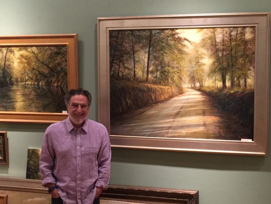 Artist Dean Gioia stands with his work in the background.