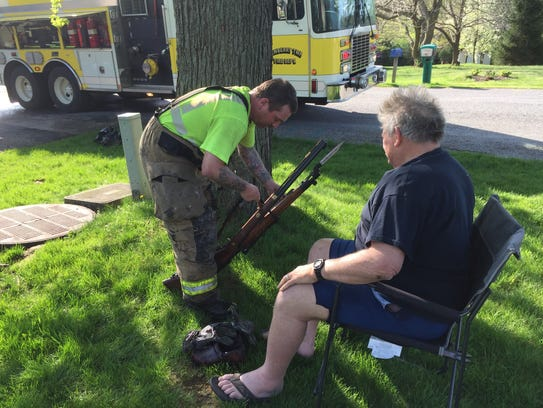 A firefighter recovers several rifles belonging to