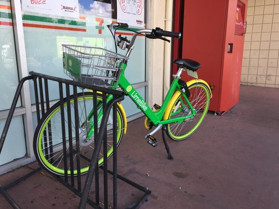 A LimeBike cycle is shown parked at a Wells Avenue