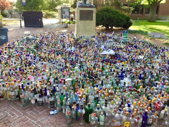 Bottles surround the statue of John Mackay at the University