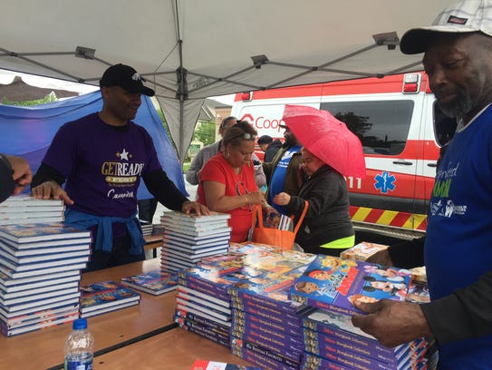 Volunteer Alex Smith (left) offers children's books