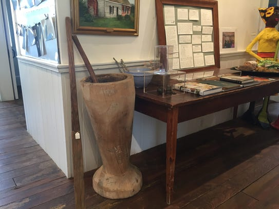 A wooden dining table, a lard paddle and a large mortar