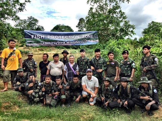 Zeb Hogan poses with military factions in Burma. He