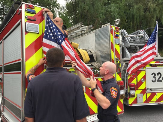 Arlington firefighters remove an American flag from