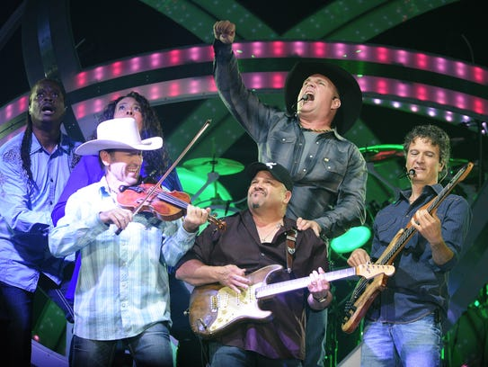 Garth Brooks, top center, is performing with his band