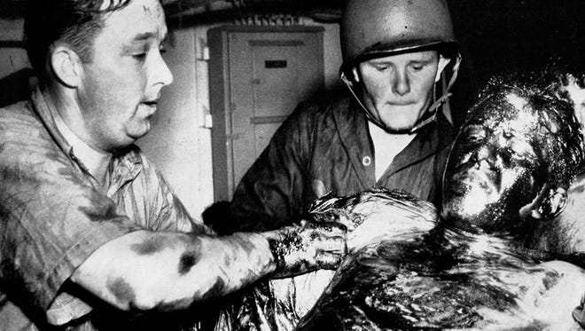U.S. Navy Corpsmen treat a survivor of the USS Indianapolis. Many who were pulled from the water were covered with oil and had infected saltwater ulcers, while also suffering from the effects of extreme dehydration, hypothermia and exposure to rough seas and intense tropical heat.