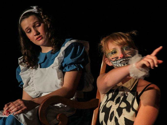 Alice (Meleah Gateley) gets directions for the Chesire Cat (Katrina Tyler) during 'Alice in Wonderland' perfmed by the Nite Lite Children's Theatre on Sunday afternoon at Milan Middle School.