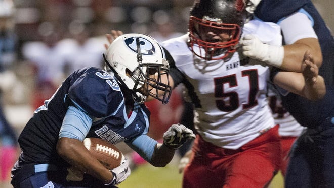 Redwood's Michael Bean tries to elude Hanford's Hunter Parks in a WYL football game at Giant Chevrolet-Cadillac Mineral King Bowl in 2015.
