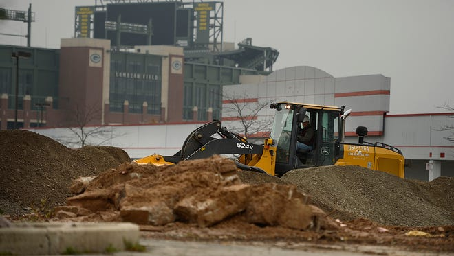 Construction crews tear up the parking lot next to the old Kmart west of Lambeau Field in Ashwaubenon on Friday, Oct. 24, 2014.