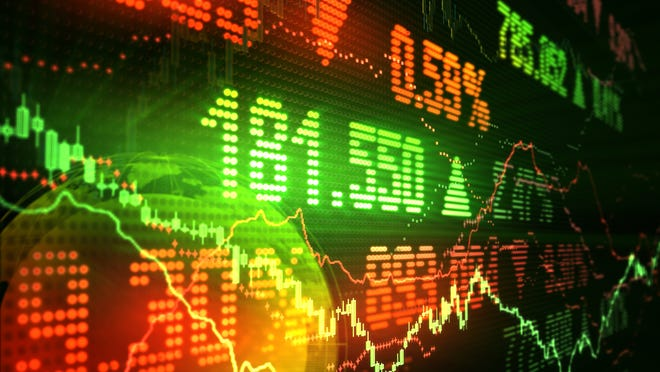 Stock market prices and charts in red and green on an LED display.