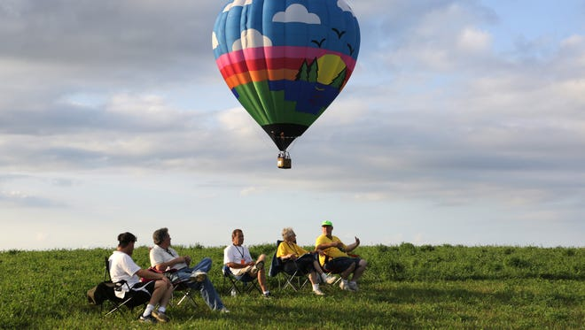 The balloon Sunny Daze piloted by Mark Spanier of Webster, Minn., flies behind a group of National Balloon Classic officials during the event Sunday in Indianola.