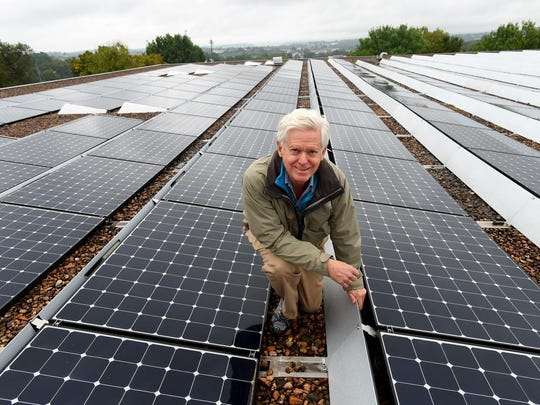 Anthony Smith, CEO and president of Secure Futures, is photographed among the several solar panels installed on top of Hartzler Library at Easter Mennonite University in Harrisonburg on Monday, Sept. 21, 2015.