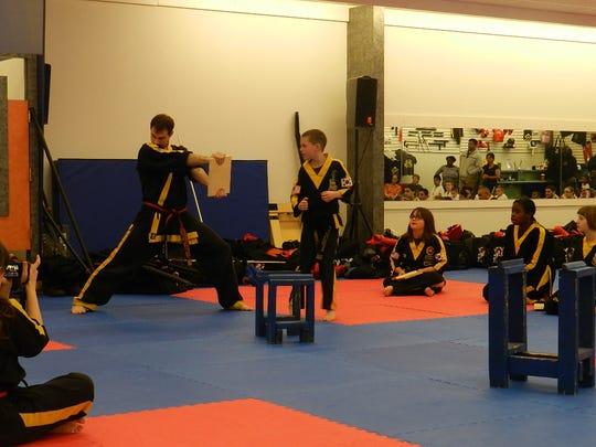 Ryan O'Callaghan splits a board during a karate class