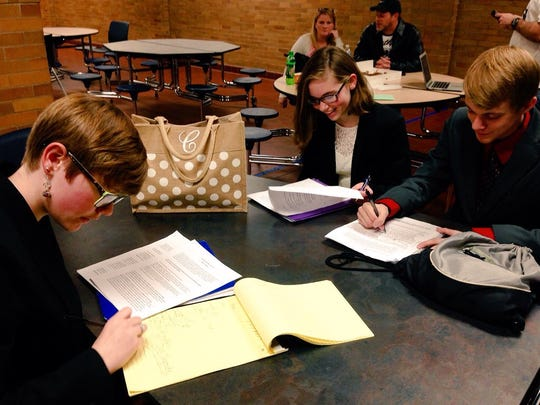 Pineville High School Speech and Debate Club members Megan Guilbeau (left), Sharon Flue (center) and Neill Roshto prepare for their next round in a tournament Saturday hosted by Bolton High School.
