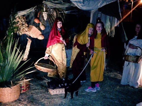 """First United Methodist Church of Alexandria members gather at a market in Bethlehem during a live nativity event Sunday. From left are """"village people"""" MollyBeth Wilkinson, Emma Marlowe, Stephanie McQuain and Katherine Douzart."""