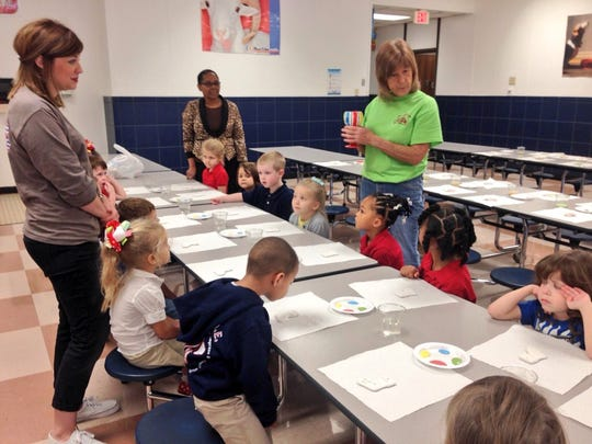 Betty Stepp (right, in green) with Funky Fleur de Lis tells Tioga Elementary pre-K students how the ornaments they paint Friday will be glazed and fired in a kiln at the store before Christmas. The class had help from their teacher Emily Welch (left) and paraprofessional Ora Sanders (back, center).