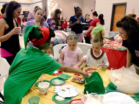 "Northwood High students and their parents decorate cookies at a parent literacy night Tuesday with the theme of ""How the Grinch Stole Christmas."""