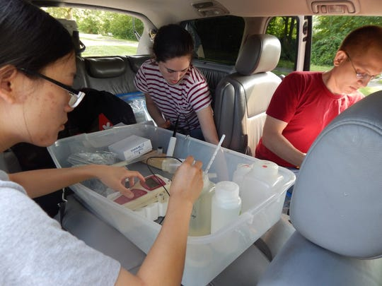 Researchers, from left, Min Tang, Bekah Martin and Dr. Otto Schwake process chemical samples and take measurements in the mobile lab during water testing in Flint on Aug. 18, 2015.