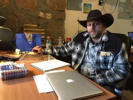 Ammon Bundy sits at a desk he's using at the Malheur