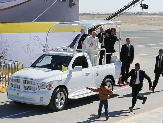 A young boy runs toward Pope Francis on Wednesday at