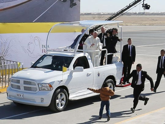 A young boy runs toward Pope Francis on Wednesday at the Juárez airport to hand him a note.