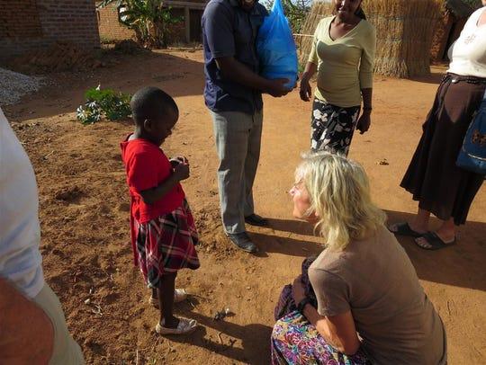 Priscilla Watts talks with five-year-old Betret Mbunda,