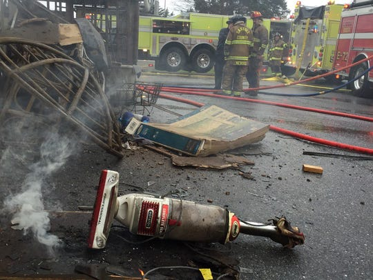 A vacuum, thrown from a window, smolders as firefighters