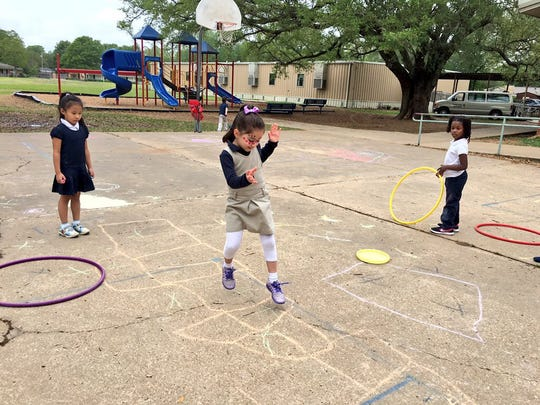 Cherokee Elementary pre-K student Jenna Musleh, 5, plays hopscotch Monday. Students could draw with sidewalk chalk, play ball, hula hoop and have their nails or faces painted Monday during Week of the Young Child.