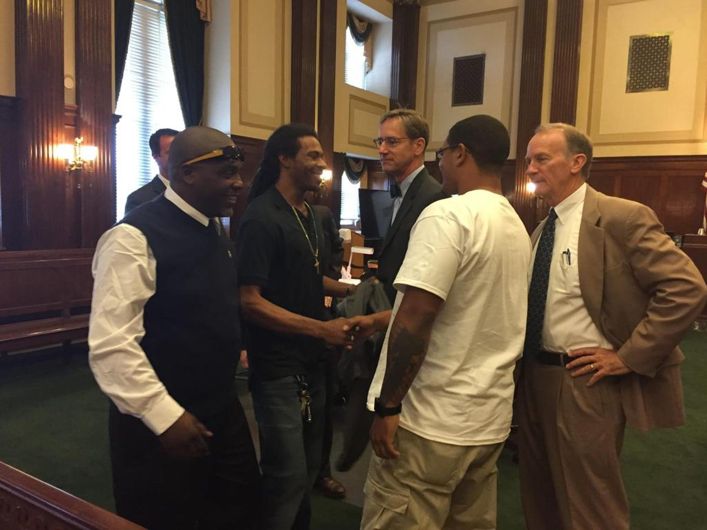 Teddy Isbell Sr., looks on as his former co-defendents, Larry Williams Jr. and Damian Mills, shake hands after a Superior Court judge found them innocent in a 15-year-old homicide. Attorneys Brad Searson and Frank Goldsmith, far right, had long argued the men were not responsible for Walter Bowman's death.