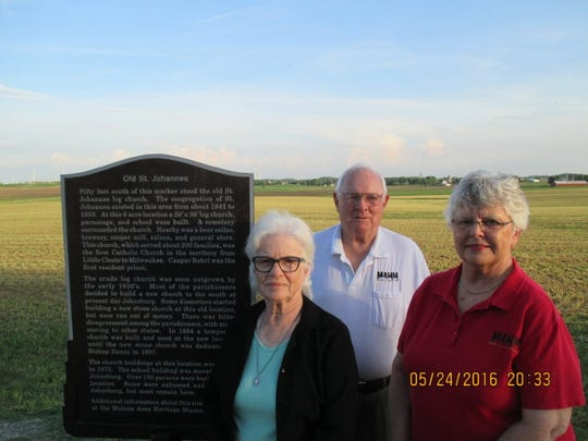 Elmer and Lorraine Thome, right, active members of the Malone Area Historical Museum, and local historian Betty Dziadek, left, are at the sign that marks the spot of the old, original Johnsburg church on Calmar Road, then known as St. Johannes. The current St. John the Baptist Church is located on the corner of highways W and Q in the village of Johnsburg.