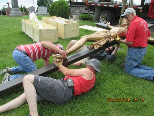 Dave Nickel, left, assists Mike Schroedl with fastening the feet of Jesus to the cross, while Chuck Schroedl assists his father, Bernie Schroedl at the top of the cross. Wenta Monument from Milwaukee installed the crucifixion scene in the church cemetery.