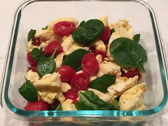 Scrambled eggs tossed with fresh spinach and cherry tomatoes.