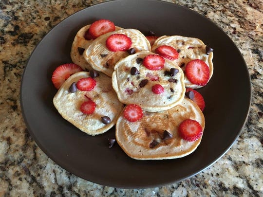 High protein Kodiak cakes with fresh strawberries in the batter topped with strawberries and dark chocolate chips.