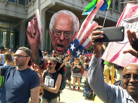 Jul 27, 2016; Philadelphia, PA, USA; A protester at a Bernie Sanders rally holds up a giant photo of the candidate during the 2016 Democratic National Convention at Wells Fargo Arena.