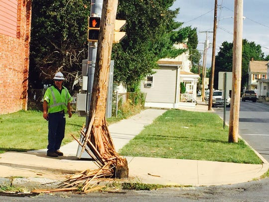 A Verizon worker stands next to a utility pole at 12th