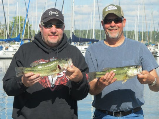 Mike King, Springfield, left, and Brad Phillips, Ozarks, display two of the bass they caught last weekend. Many anglers are finding out that fall fishing can be very good.