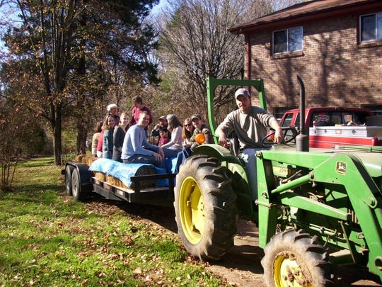 Matthew Rhoads driving a tractor on the family farm.